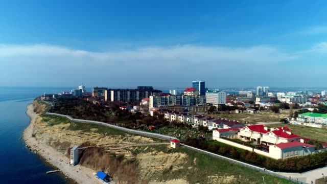 Coastal resort town in Russia, Anapa at sunny day. Mountains waterfront with sea view, aerial footage.