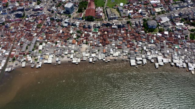 coastal slums with contaminated water in indonesia. aerial shot - индонезия стоковые видео и кадры b-roll