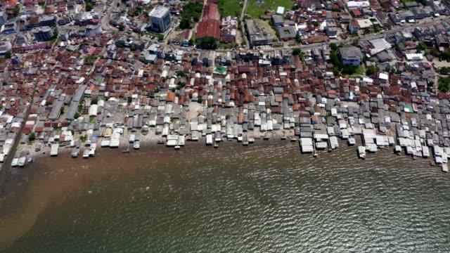 vidéos et rushes de bidonvilles côtiers avec de l'eau contaminée en indonésie. tir aérien - indonésie