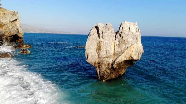 coastline, mediterranean sea,  rocks Camera moves around a beautiful rock, revealing the coastline of mediterranean sea. greek islands stock videos & royalty-free footage