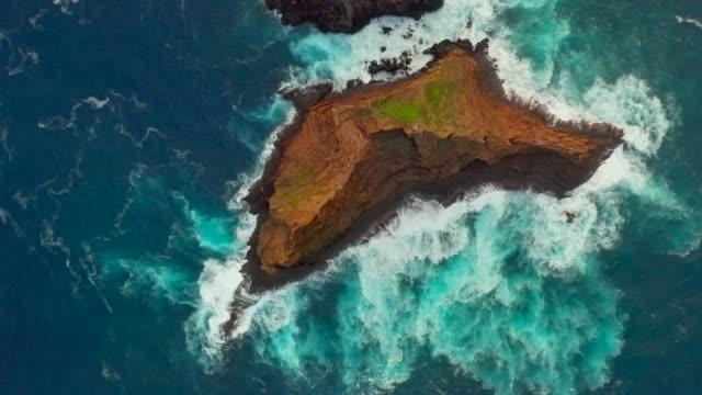 vídeos de stock e filmes b-roll de coastline with ocean and rocks near remote island - ilha da madeira