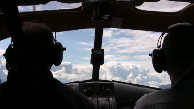 Cockpit View of Seaplane Flying Into Clouds Taken from inside a low flying float plane.  View from behind the pilot and through the front window, as we're zooming into the approaching clouds. propeller airplane stock videos & royalty-free footage