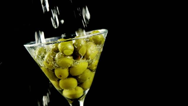 stockvideo's en b-roll-footage met cocktail wordt gegoten in het glas vol met olijven - martiniglas
