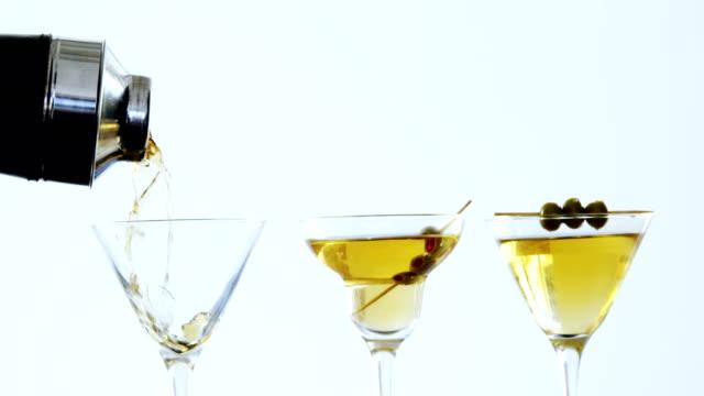 stockvideo's en b-roll-footage met cocktail wordt gegoten in drie glazen - martiniglas