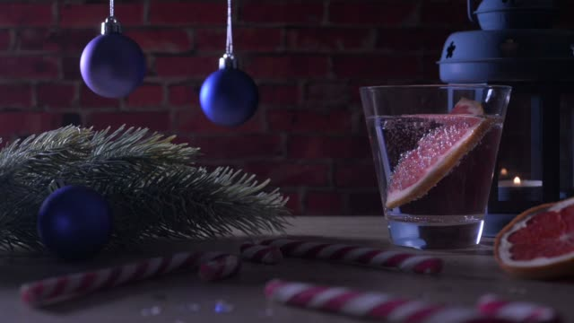 Cocktail Grapefruit, candle, fir branch with christmas toys and candy canes on a red brick video