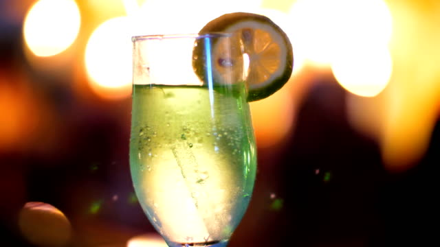 cocktail party, drink with ice, in a glass with a straw and decorated with a slice of lemon, in the rays of soffits, lamps, flickering lights. original alcoholic and non-alcoholic cocktails video