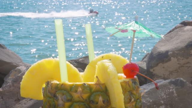 cocktail, serviert in einer frischen ananas mit dem ozean im hintergrund sekt - spring break stock-videos und b-roll-filmmaterial