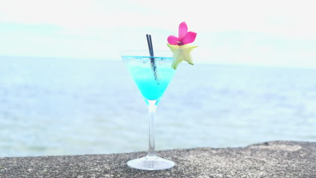 cocktail with blue liqueur alcohol in a martini glass with two black straws and garnish of star fruit and pink flower petals, with sea in background video