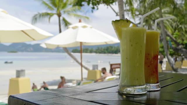 cocktail glas auf tisch mit blick auf strand und meer - tropischer cocktail stock-videos und b-roll-filmmaterial