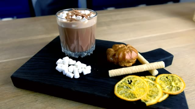 Cocoa with marshmallow in rock glass on a wood black tray with cake and lemon. Close-up side view. video