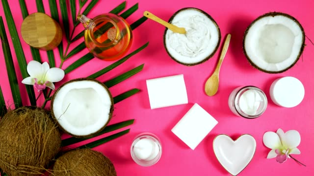 coconut cosmetics with soaps, moisturizers, beauty products on pink background. - stan naturalny filmów i materiałów b-roll