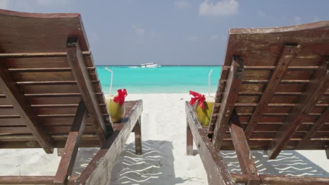 ms-coconut getränke auf den liegestühlen am sonnigen, ruhigen tropischen ocean beach, malediven - sun chair stock-videos und b-roll-filmmaterial