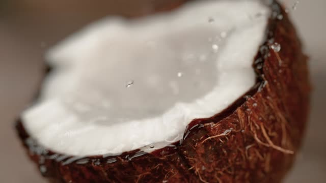 stockvideo's en b-roll-footage met macro kokosnoot sap spatten over de kokosnoot met ongerepte vlees en bruine schil - tropisch fruit