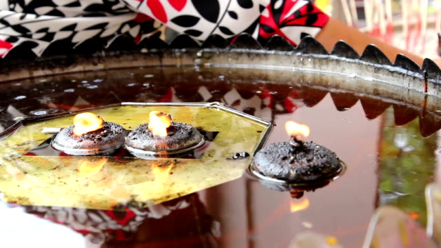 Coconut oil lamp and joss sticks burning at Thai temple ,Bangkok video