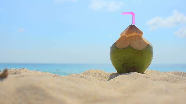 Coconut with drinking straw on a beach close up coconut with drinking straw on a beach at Surin beach, Phuket , Thailand coconut stock videos & royalty-free footage
