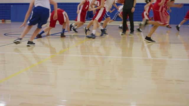 vídeos y material grabado en eventos de stock de equipo de baloncesto mixto funcionando líneas en un gimnasio - deportes de la escuela secundaria
