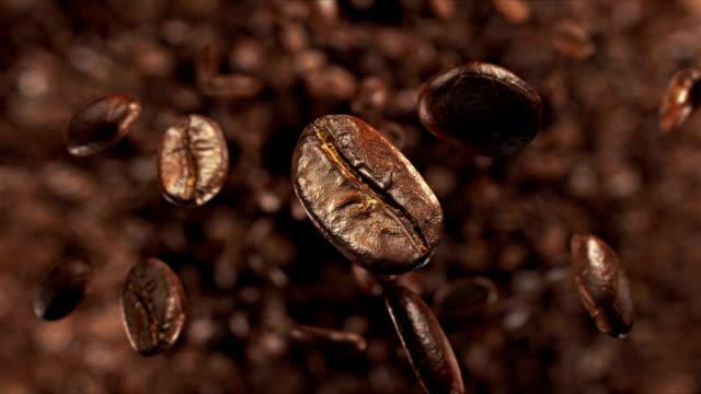 kaffeebohnen-explosion in superzeitlupe 4k - rohe kaffeebohne stock-videos und b-roll-filmmaterial