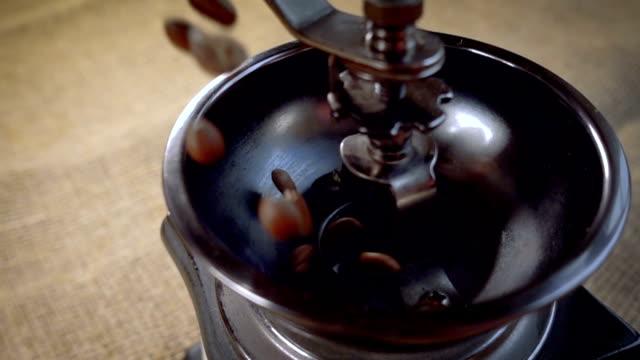 vídeos y material grabado en eventos de stock de caída de granos de café en el molino viejo. con el tiro de seguimiento de rotación lenta. - grind