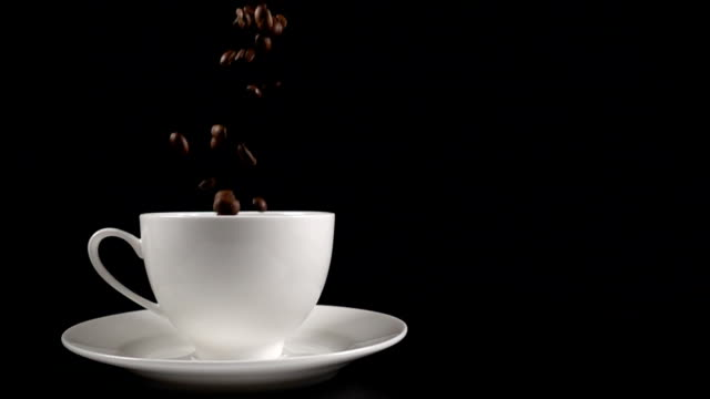 Coffee beans falling into a white cup video
