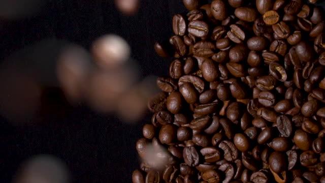 kaffeebohnen fallen auf kaffeehaufen - rohe kaffeebohne stock-videos und b-roll-filmmaterial