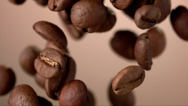 coffee beans falling over background (super slow motion) - coffee stok videoları ve detay görüntü çekimi