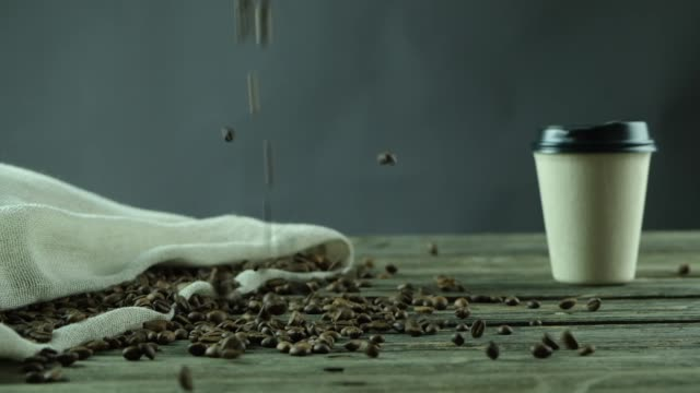 coffee beans fallings on a wooden table beside a beige bag full of coffee beans along side a coffe cup in studio