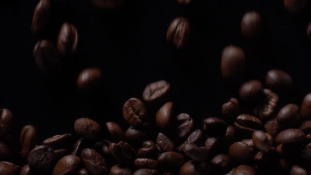 Coffee beans filling full on black background Horizontal view of Coffee beans filling full in slow motion with black background coffee stock videos & royalty-free footage