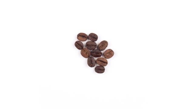 kaffeebohnen herzform auf weißem hintergrund - geröstete kaffeebohne stock-videos und b-roll-filmmaterial