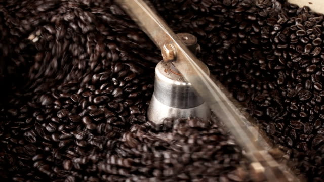 Coffee beans in a large coffee roaster being poured video