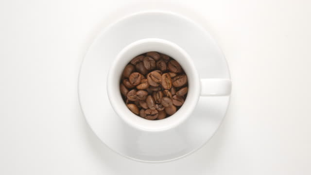 TOP VIEW: Coffee beans in a white cup (stop motion) video