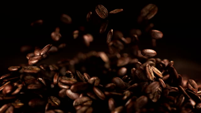 coffee beans jumping in super slow motion 4k - coffee стоковые видео и кадры b-roll