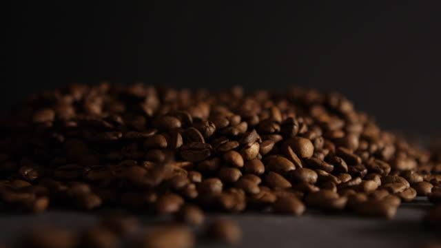 kaffeebohnen am schwarzen tisch - schwarzer kaffee stock-videos und b-roll-filmmaterial