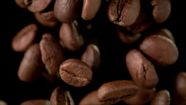 coffee beans over black background (super slow motion) - coffee stok videoları ve detay görüntü çekimi