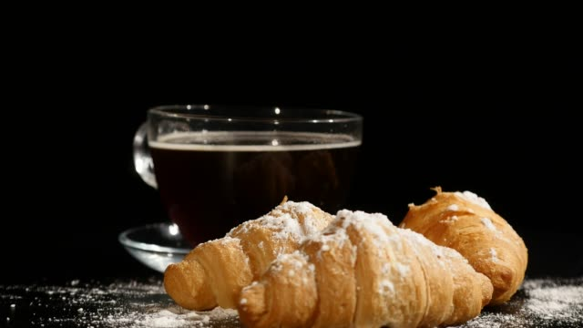 coffee break times. croissants and coffee rotate on a black background - piattino video stock e b–roll