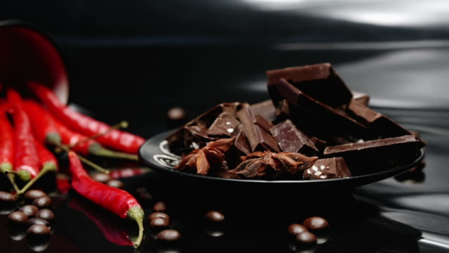 Coffee, chocolate and chili over black Pieces of dark chocolate, roasted coffee beans and red chili peppers scattered off black cup on reflective glossy black background. Circle dolly shot chili pepper stock videos & royalty-free footage