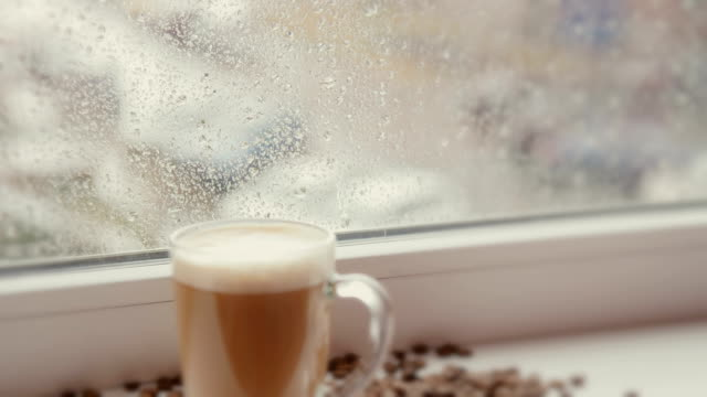 Coffee cup against window with rainy day view video