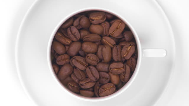 HD Coffee cup filled with roasted beans HD Coffee cup filled with roasted beans turning, isolated on white background.   kaffee stock videos & royalty-free footage
