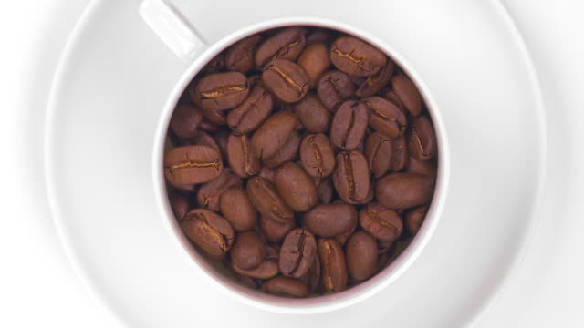 Coffee cup filled with roasted beans Zoom in of coffee cup filled with roasted beans turning, isolated on white background (HD, NTSC, PAL). kaffee stock videos & royalty-free footage