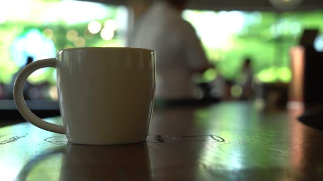 vídeos de stock e filmes b-roll de copo de café no café - bar local de entretenimento