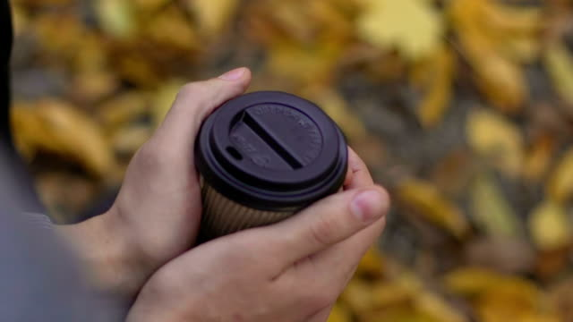 Coffee cup in man hands, male feeling lonely and sad in the park, break up video