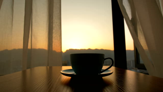 Coffee cup on table against background of sunrise