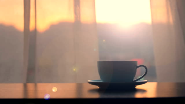 Coffee cup on table with sunset window background