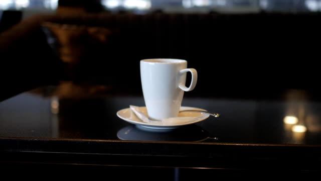 vídeos de stock, filmes e b-roll de copo de café sobre a mesa no restaurante - moda parisiense