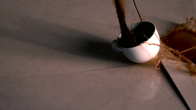 Coffee cup smashing onto surface and cracking it video