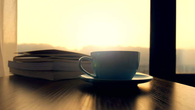 Coffee cup with book on table