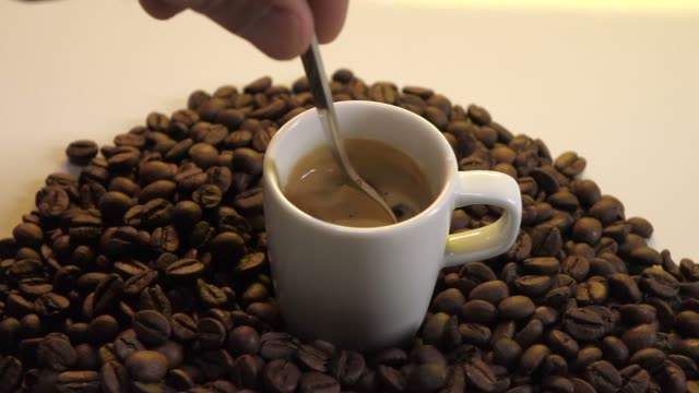 Coffee cup with coffee beans and spoon that turns sugar video