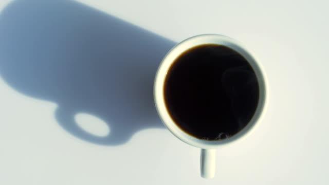 tazza di caffè con vapore naturale su tavolo bianco dall'alto - pausa caffè video stock e b–roll