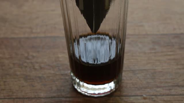vidéos et rushes de goutte à café mélangé par de l'eau chaude tombant sur le verre - pots de bureau
