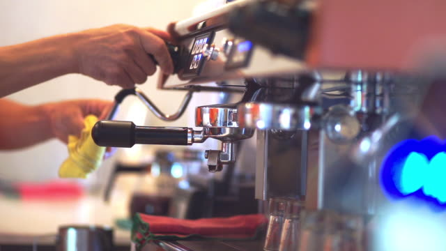Coffee dripping from machine into cup by a Barista.