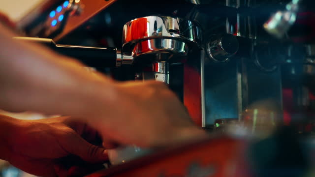 Coffee drips from the machine into cup by a Barista at the coffee shop